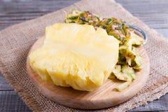 Резать свежий ананас на старой деревянной предпосылке Стоковые Изображения