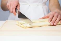 Резать сырцовое тесто в муке с ножом Стоковые Фотографии RF