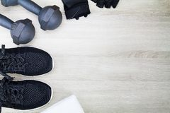 Резвитесь ботинки, гантели, белое полотенце и перчатки фитнеса на деревянной предпосылке Стоковые Фотографии RF