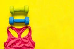 Резвитесь верхняя часть, футболка спорта, 2 гантели на желтой предпосылке, плоско Стоковые Изображения