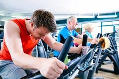 Резвитесь в спортзале - закручивать людей велосипедов фитнеса стоковые фото