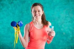 Резвитесь девушка фитнеса с гантелями, бутылка воды и рулетка для диеты - на предпосылке бирюзы Помадки u Стоковая Фотография RF