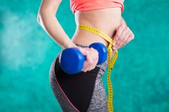 Резвитесь девушка фитнеса с гантелями и рулеткой для диеты - изолированной на предпосылке бирюзы Стоковые Фотографии RF