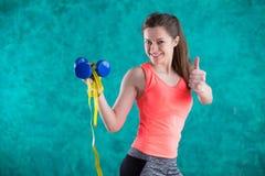 Резвитесь девушка фитнеса с гантелями и рулеткой для диеты - изолированной на предпосылке бирюзы Стоковое Изображение RF