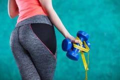 Резвитесь девушка фитнеса с гантелями и рулеткой для диеты - изолированной на предпосылке бирюзы Стоковые Фото