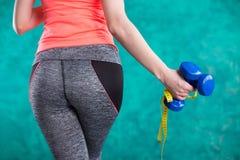 Резвитесь девушка фитнеса с гантелями и рулеткой для диеты - изолированной на предпосылке бирюзы Стоковые Изображения
