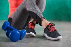 Резвитесь девушка фитнеса с гантелями - на предпосылке бирюзы Стоковая Фотография