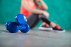 Резвитесь девушка фитнеса с гантелями - на предпосылке бирюзы Стоковые Фотографии RF