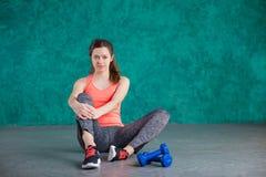 Резвитесь девушка фитнеса с гантелями - на предпосылке бирюзы Стоковое фото RF