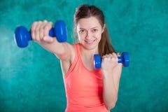 Резвитесь девушка фитнеса с гантелями - на предпосылке бирюзы Стоковые Фото