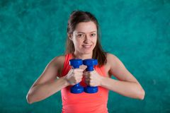 Резвитесь девушка фитнеса с гантелями - на предпосылке бирюзы Стоковое Фото