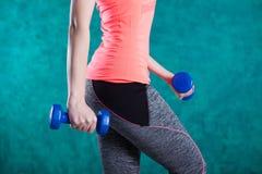 Резвитесь девушка фитнеса с гантелями - на предпосылке бирюзы Стоковое Изображение