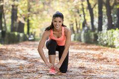 Резвитесь женщина бегуна связывая ее шнурки тапки ботинка усмехаться счастливый подготавливает для бежать и jogging разминки на г Стоковые Фотографии RF