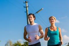Резвитесь пары бежать и jogging на сельской улице стоковая фотография rf