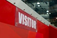 Резвитесь ` посетителя ` знака на стене в центре ratiocination Знак прозрачен с белыми характерами на красной предпосылке стоковая фотография