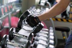 Резвитесь человек делая строки гантели одн-руки металла в современном спортзале Стоковая Фотография