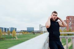 Резвитесь человек фитнеса представляя против фона города Мужской парк падения снаружи спортсмена подходящая модель Стоковое фото RF