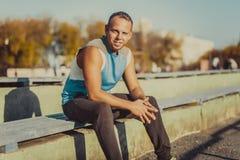 Резвиться привлекательный человек сидя на стенде и Стоковое фото RF