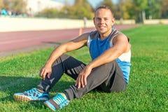 Резвиться привлекательный человек сидя на траве и остатках в стадионе Стоковое Изображение