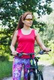 Резвит женщина с велосипедом на прогулке Стоковые Фотографии RF