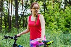 Резвит женщина с велосипедом на прогулке Стоковое фото RF