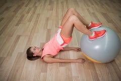 Резвит женщина с шариком пригонки Девушка делая тренировки ноги на предпосылке пола уклад жизни принципиальной схемы здоровый ско Стоковые Фото