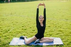 Резвит йога практик девушки на парке Стоковая Фотография