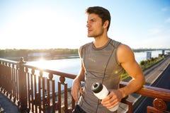 Резвит человек отдыхая после бежать пока полагающся против перил моста Стоковые Фотографии RF