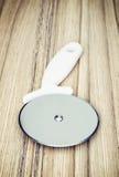 Резец пиццы на деревянной предпосылке Стоковые Фотографии RF