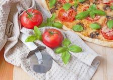 Резец пиццы, томаты и итальянская пицца Стоковые Изображения