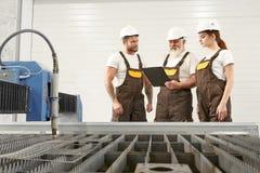 Резец плазмы и 3 инженера говорить, смотря папку стоковое фото