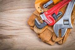 Резец трубы универсального гаечного ключа разводного гаечного ключа перчаток безопасности на wo Стоковая Фотография