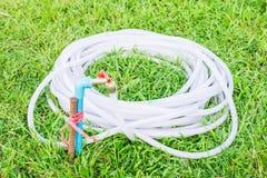 Резиновая трубка с постаретым faucet на поле зеленой травы Стоковые Фотографии RF