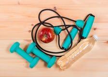 Резиновый детандер, гантели, яблоко и бутылка воды Стоковое Фото