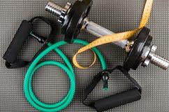 Резиновый трубчатый детандер, регулируемая гантель и лента измерений Стоковые Фото