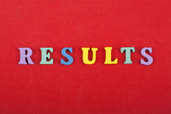 РЕЗУЛЬТАТЫ формулируют на красной предпосылке составленной от писем красочного блока алфавита abc деревянных, копируют космос для стоковая фотография rf