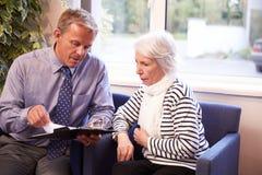 Результаты теста доктора Discussing с старшим женским пациентом Стоковое Изображение