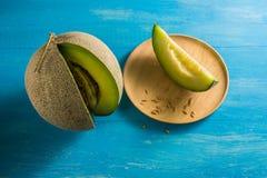 Результаты дыни Размещенный на голубых деревянных столах и доле вне часть на шаре Брайна деревянном Стоковое Изображение RF