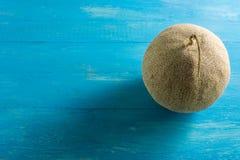 Результаты дыни Размещенный на сини деревянного стола Стоковое Фото