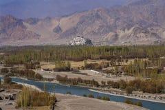 Река в голубой подаче цвета через обрабатываемые земли с деревьями в осени Стоковые Изображения