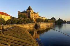 Река Влтавы и старые исторические здания на своем левом береге во время захода солнца в Праге, чехии Стоковые Изображения