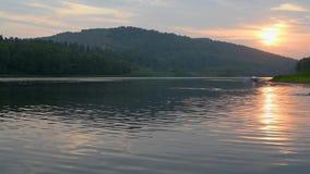 Река в теплых лучах заходящего солнца с отражением неба видеоматериал