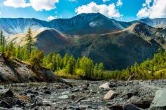 Река горы на ноге гребня покрашенного в солнечном летнем дне Стоковые Изображения