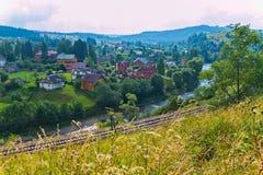 Река горы разделено железной дорогой от одной деревни стороны и деревни на другом стоковые изображения