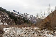 Река горы среди больших камней в предыдущей зиме Стоковое фото RF