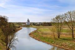 Река деревни на предпосылке церков на лете Стоковые Изображения