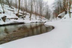 Река зимы в прикарпатских горах с покрытыми снег банками Стоковые Изображения
