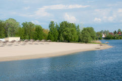 Река и песчаный пляж с зонтиками Стоковая Фотография