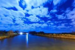 Река на ноче, с залитыми лунным светом облаками в небе выше стоковое изображение rf