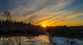 Река на предпосылке захода солнца Стоковая Фотография RF